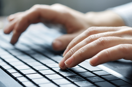 Photo of hands typing a research proposal